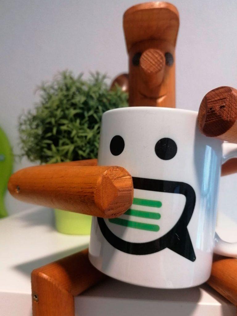 muñeco de madera con una taza con el logo de Haz Marca